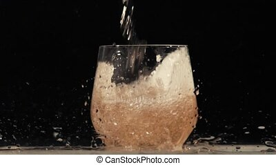 Flowing wine on black background in slow motion