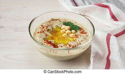 A bowl of creamy hummus with olive oil. - A bowl of creamy...