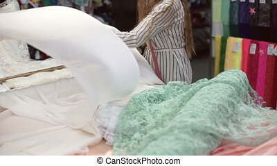 Fabric store worker unwraps roll white atlas tissue indoors....
