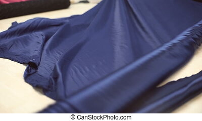 Roll of dark blue silk material unfolding on special table.