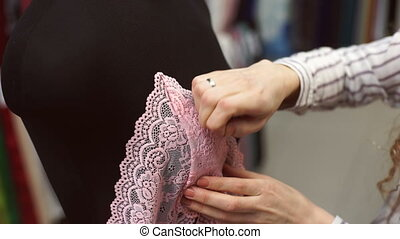Tissue seller prepares black soft mannequin with pink lace satin