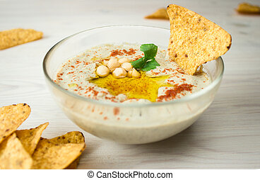 A bowl of creamy hummus with olive oil and chips. - A bowl...