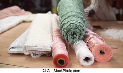 Woman collect rolls of different fabric together on wooden table.