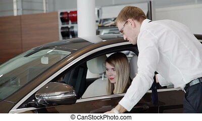 In the showroom woman sitting in a brown car, which the...