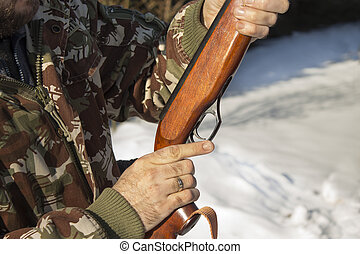 Hunter hunting reload firearms in the winter scenery.
