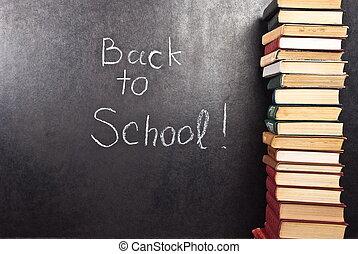 Back to school written on chalkboard witch books