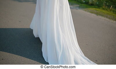 Young woman in white dress posing outdoor walking on the...