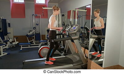 Attractive European girl running on the treadmill in the...