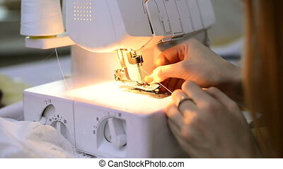Seamstress quickly inserts a thread with tweezers white overlock.