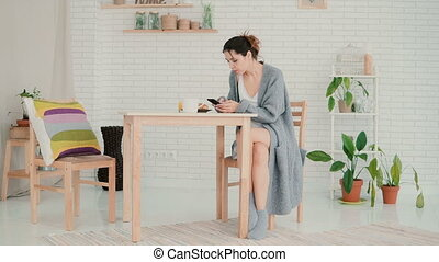 Happy woman sitting in kitchen wearing pajamas and surfing the Internet. Brunette girl uses smartphone and drinks coffee