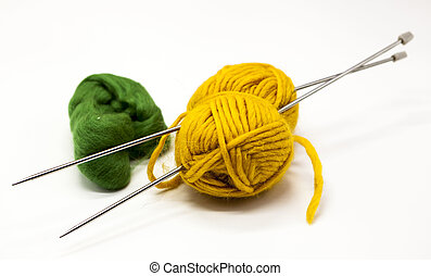 Green and yellow balls of yarn for knitting with spokes on a...