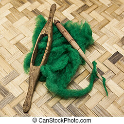 Green wool and old spindle close-up on wooden background....