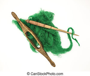 Green wool and old spindle close-up on white background....
