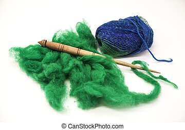 Green wool, blue thread and old spindle close-up on white...