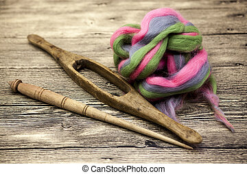 Colored hair and old spindle close-up on wooden background....