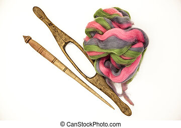 Colored hair and old spindle close-up on white background....