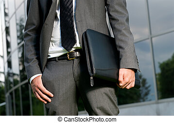 Unrecognizable businessman with suitcase close-up on a modern building background