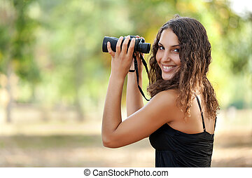 woman watching wildlife - beautiful young woman holding...