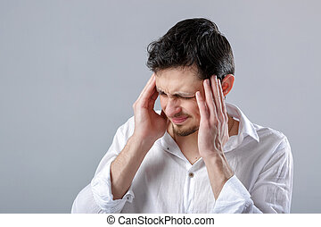 Frustrated young brunette man in shirt with headache on gray...