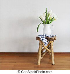 With tulips bouquet in white vase on wooden rustic chair -...