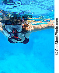 Snorkeling - Woman swimming under water in snorkeling mask...