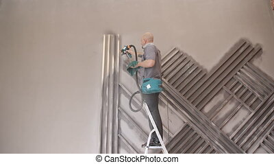 A man stands on a ladder and paint spray detail design...