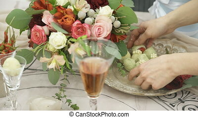 Florist puts flowers in a vase to decorate the table in the triumph.