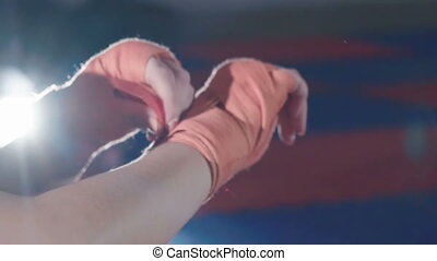 Close up of woman putting on red punching wraps in fitness studio. Slowly