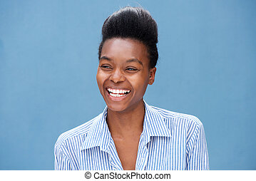 portrait of beautiful young black woman laughing against blue wall