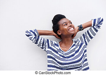 happy young black woman smiling with hands behind head