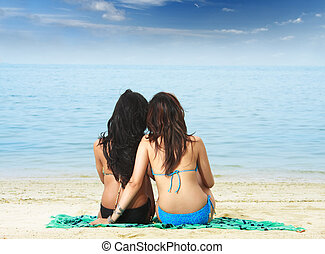 friends at tropical paradise - two girls sitting by the...