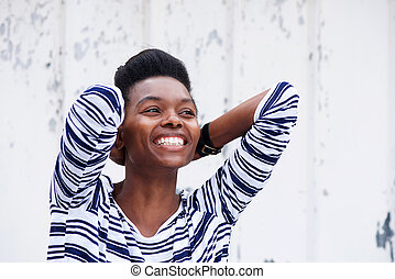 cheerful young woman smiling with hands behind head