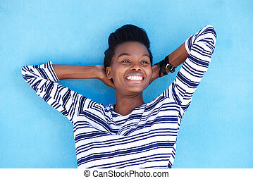 smiling young black woman with hands behind head