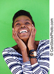 young woman laughing with hands on face