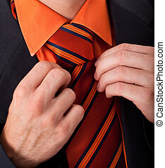 Detail of a man, fixing his tie 1