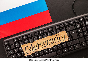 CYBERSECURITY, inscription on torn white paper sheet, on a...