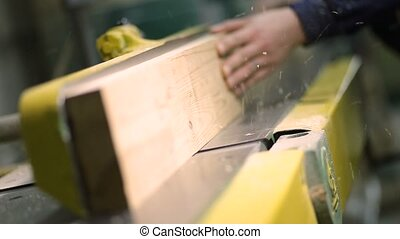 Carpenter working with electric planer on plank