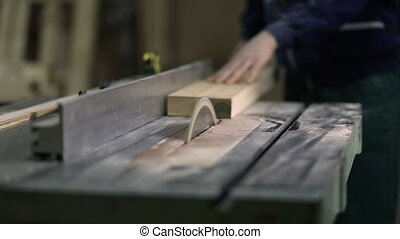 Carpenter working on electric saw cutting boards - Carpenter...