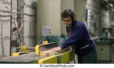 Carpenter working on sawing table in workshop - Carpenter...