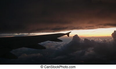The plane flies into thick dark gray clouds. Evening view from the airplane window.