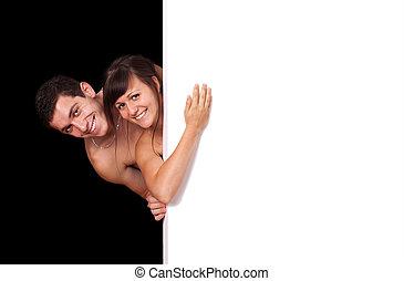 A cute couple behind a white wall