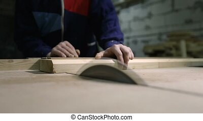 Carpenter cutting wooden plank with table saw - Closeup...