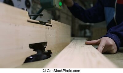 Carpenter engaged in processing wood in workshop - Closeup...
