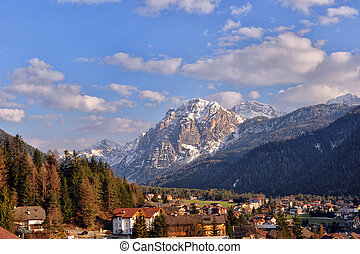 Landscape of Dolomites mountains in summer with a typical village and meadows