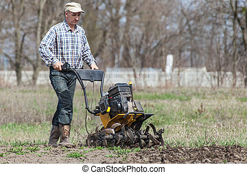 Farmer loosens the soil cultivator - Man working in the...