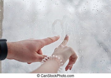 Hands draws love heart on cold fogged window, closeup