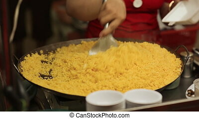 The girl stirs the yellow rice and puts it in a container. Close-up