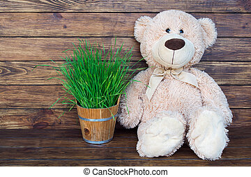 Brown teddy bear sitting on a wooden brown background with...