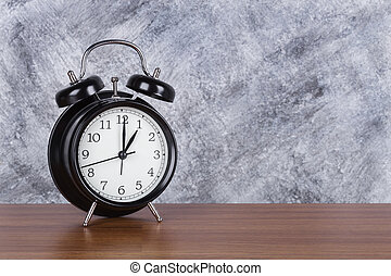1 o'clock vintage clock on wood table and wall background