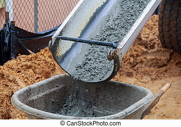Worker pouring concrete to formwork at construction